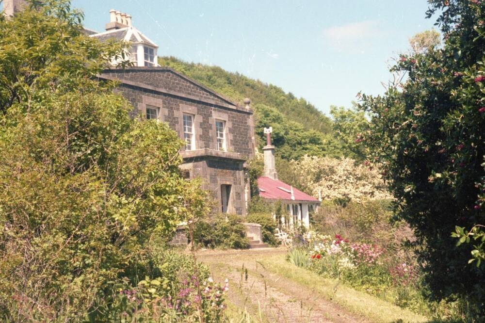 An early colour photograph of Canna House, seen from the garden on a sunny day.