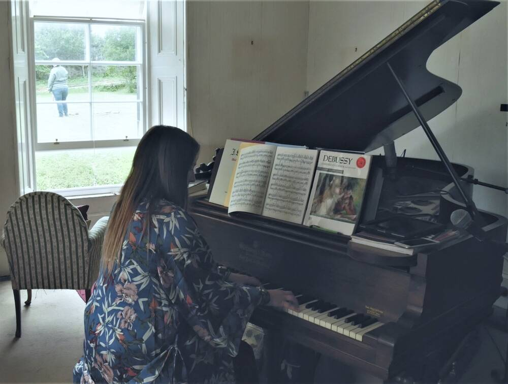 A lady sits at a piano, with its lid propped up. Sheets of music and a Debussy book rest on the piano. The piano is next to an open window, through which a lady can be seen in the garden.