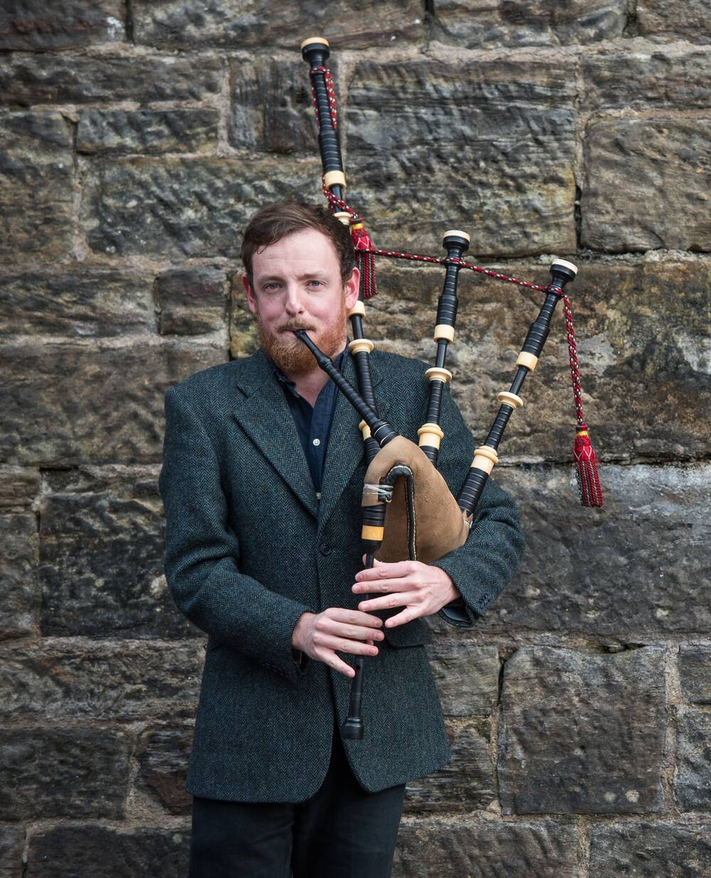 A man wearing a tweed jacket plays the bagpipes, standing in front of a stone wall.