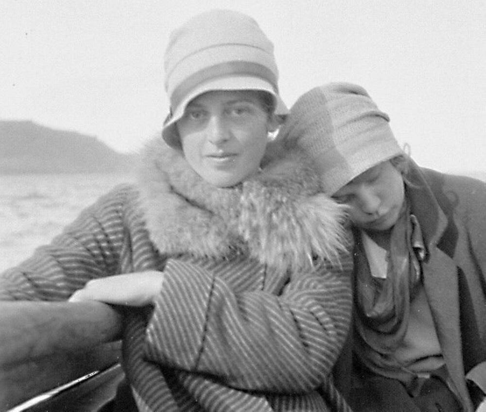 Two women sit on a boat. The lady to the left looks directly at the camera; the lady on the right has her eyes closed and rests her head on her friend's shoulder.