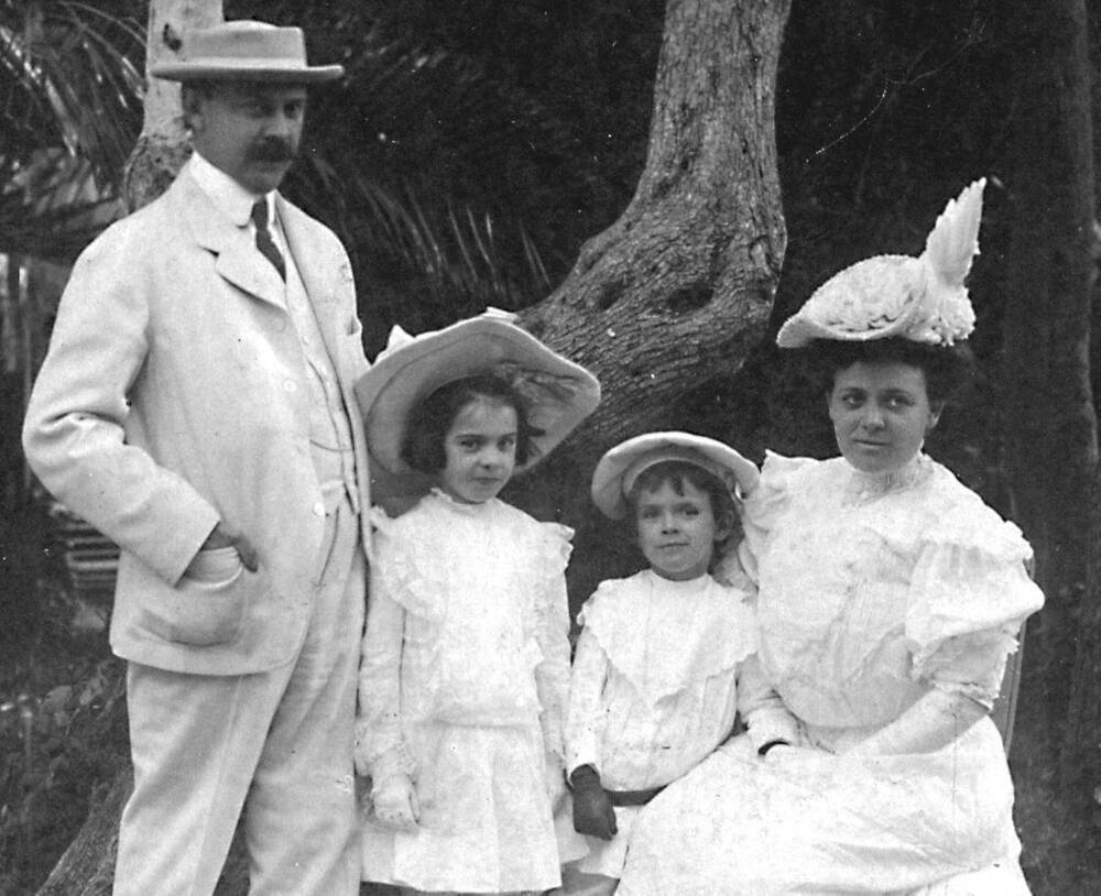 A family pose for a photograph, all wearing Easter bonnets. The man stands to the left, next to a young girl, a smaller boy and then a seated lady on the right. The lady wears an elaborate hat shaped like a swan.