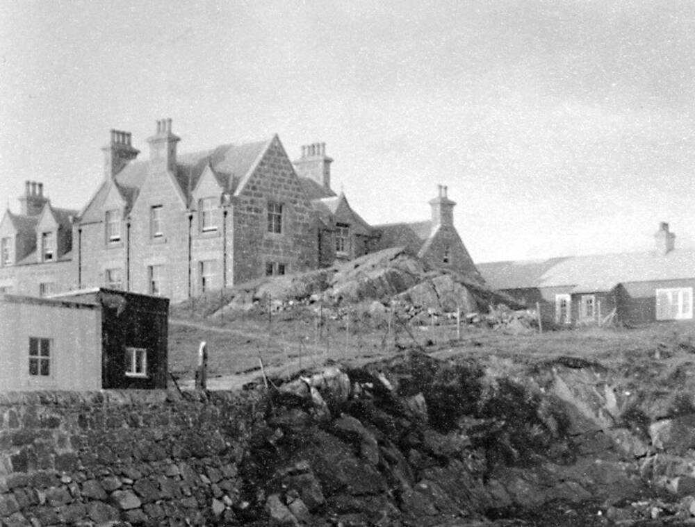A black-and-white photograph of the Lochboisdale Hotel. The sea wall, fenced at the top, is shown in the foreground.