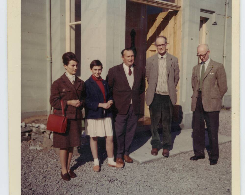 A colour photograph of three men and two women standing outside a grand stone building in the 1960s.