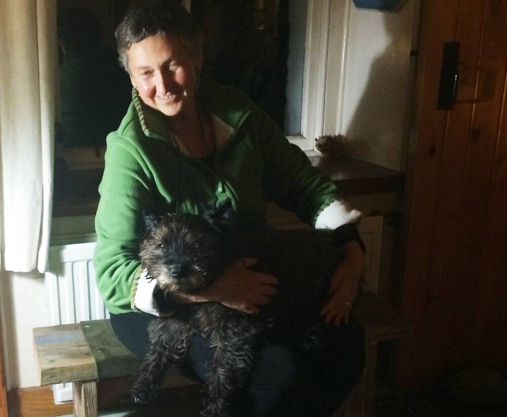 A woman sits on a wooden bench inside a porch. She cuddles a black terrier on her lap.