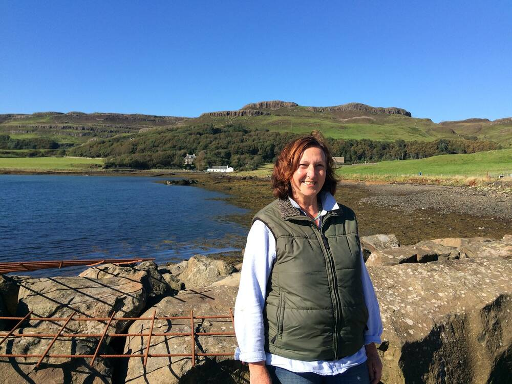 A woman stands on a stone pier, smiling at the camera. Hills and woods can be seen in the background, on a bright sunny day.