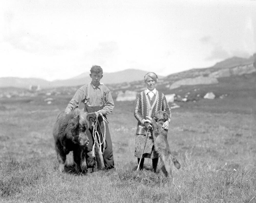 A black and white photo of a young man and a woman standing in a field. The man is holding a calf on a rope; a dog is jumping up at the woman and resting its paws on her cane.