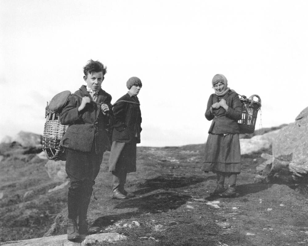 Two women and a boy pose with kelp baskets on their backs.
