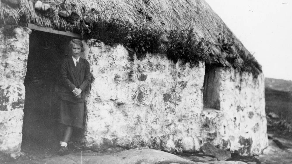A black and white photo of a young lady standing in the doorway of a thatched cottage. She stands with her legs crossed at the ankle, and her hands folded in front of her.