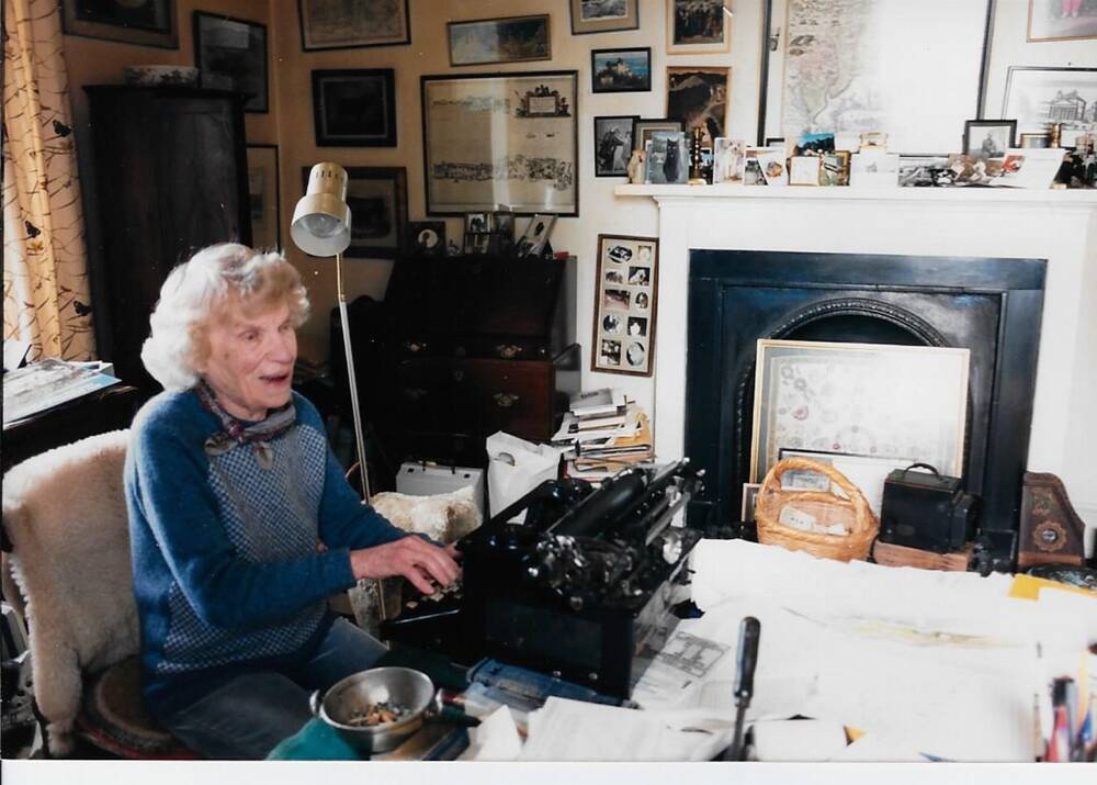 Margaret sits at a typewriter at a paper-covered desk. A tall anglepoise lamp stands beside her.