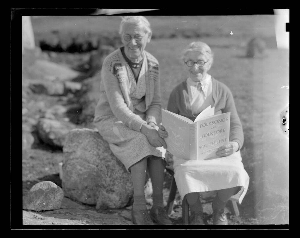 A black and white photograph of two elderly, smiling women. They are sitting outdoors on a boulder and a stool, and the lady on the right holds a large book open on her lap.