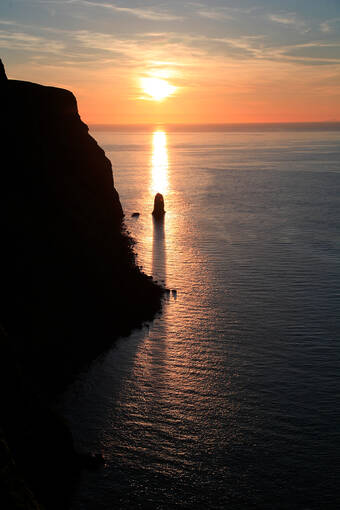 Cliffs silhouetted by the sunsetting over the sea.