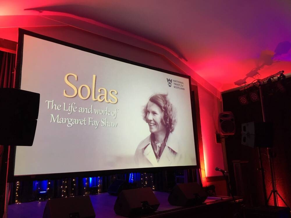 A large screen displays the title screen for the film 'Solas', which features a photograph of a smiling Margaret Fay Shaw. The screening is in a room lit with purple and red lights.