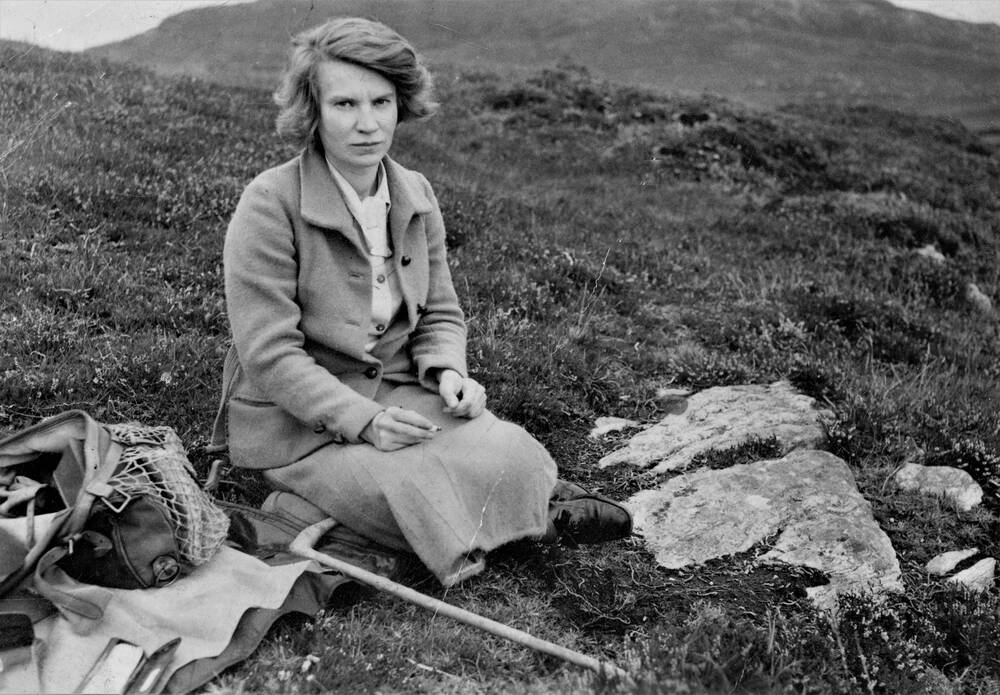 A black and white photograph of Margaret Fay Shaw, sitting on a hillside. A bag and coat lie on the ground beside her.