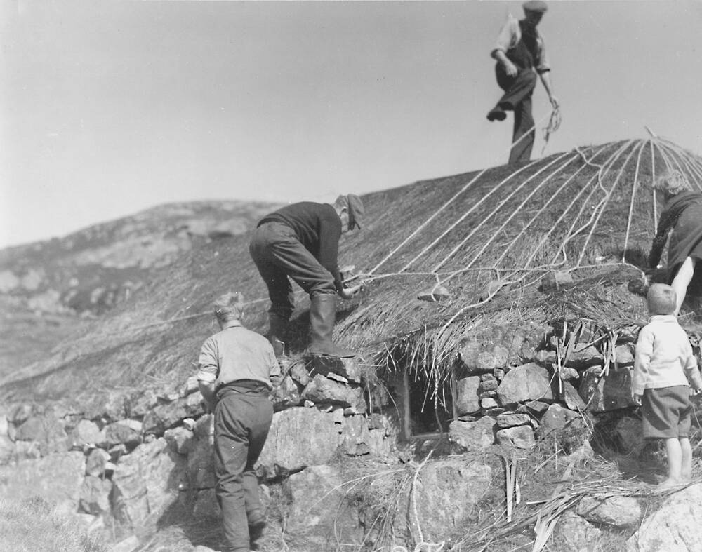 A black and white photo of men and women working on a thatched roof. A man stands at the top, holding a rope. Another pegs it down by the top of the wall. A small boy stands to the side, watching.