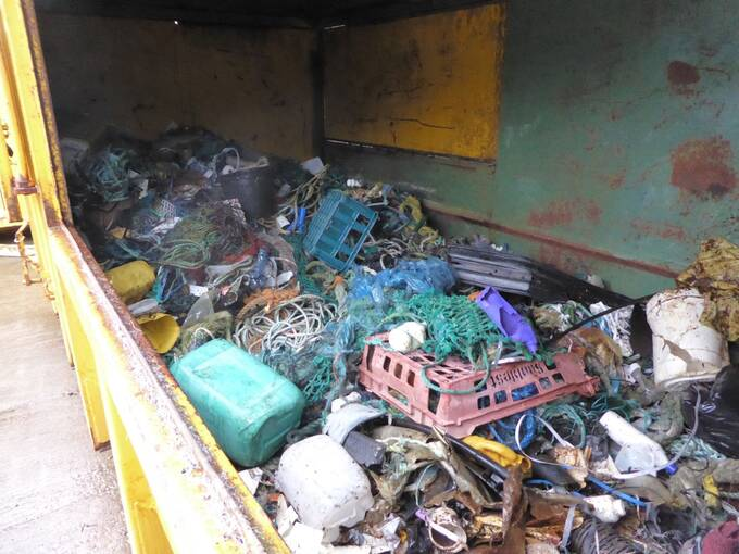 A skip on Canna, filled with rubbish collected from the beaches. There are a lot of plastic pallets, fishing rope, plastic bottles and containers.