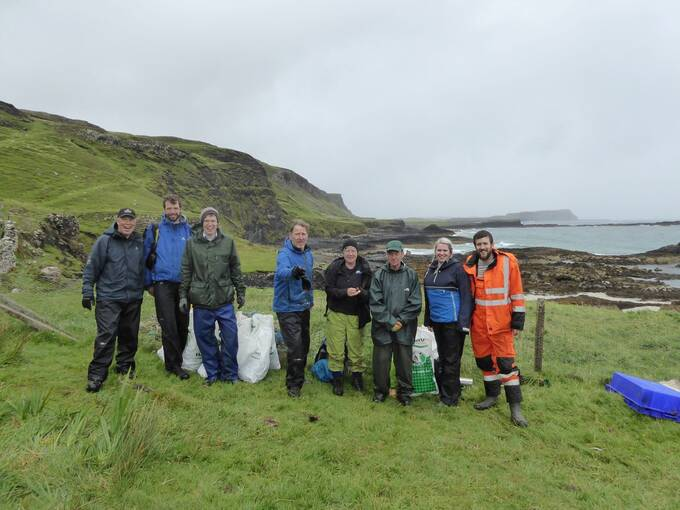 8 people stand in front of a wire fence in a field beside a beach on Canna. It is a grey day and all are wearing waterproofs. Large rubbish sacks stand behind them, as well as a large blue plastic tray just to the right of the picture.