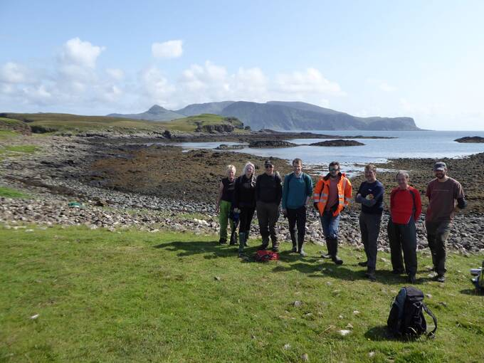 8 people stand in a line at the edge of a field on a sunny day on Canna. Behind them lies a rocky beach, where the tide is out.