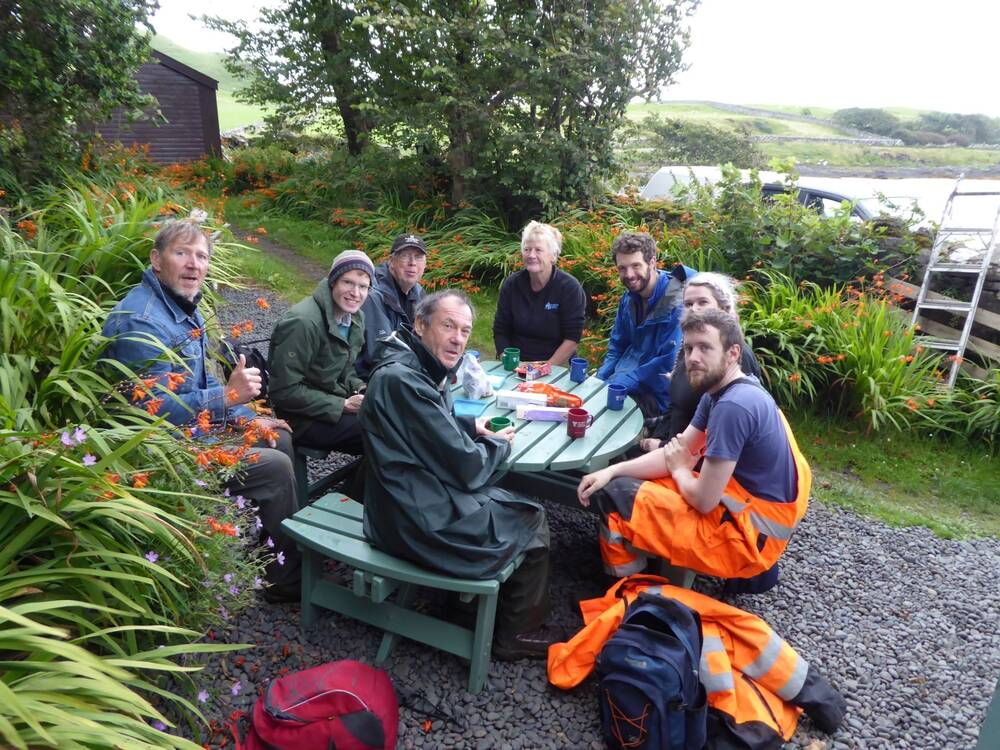 Eight people sit around a circular wooden picnic bench on Canna, enjoying mugs of tea and biscuits.