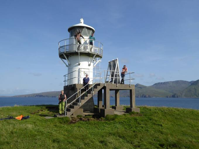 Five people stand at a lighthouse in a field on Canna on a bright sunny day. The sea is in the background. A set of steps lead up to a platform attached to the lighthouse.