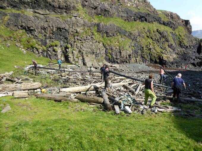 Seven people carry a very long, black plastic pipe on the shore on Canna. The beach contains many pieces of driftwood, over which the volunteers are clambering.