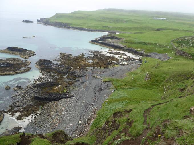 An aerial view of a section of coastline on Canna, showing a stony beach, rockpools and grassy fields. Only driftwood is visible at the high tide line.
