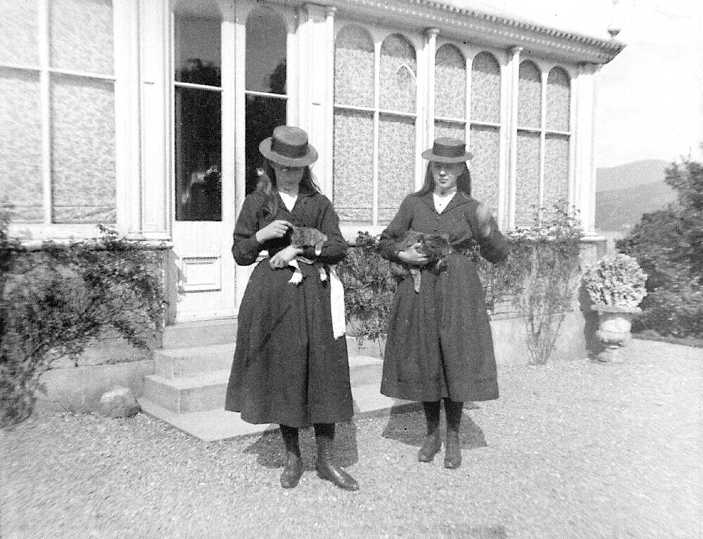 A black and white photograph of two teenage girls standing outside a decorative building, in a gravelled courtyard. Both hold a kitten in their arms. The girls wear long black coats and boater-style hats.