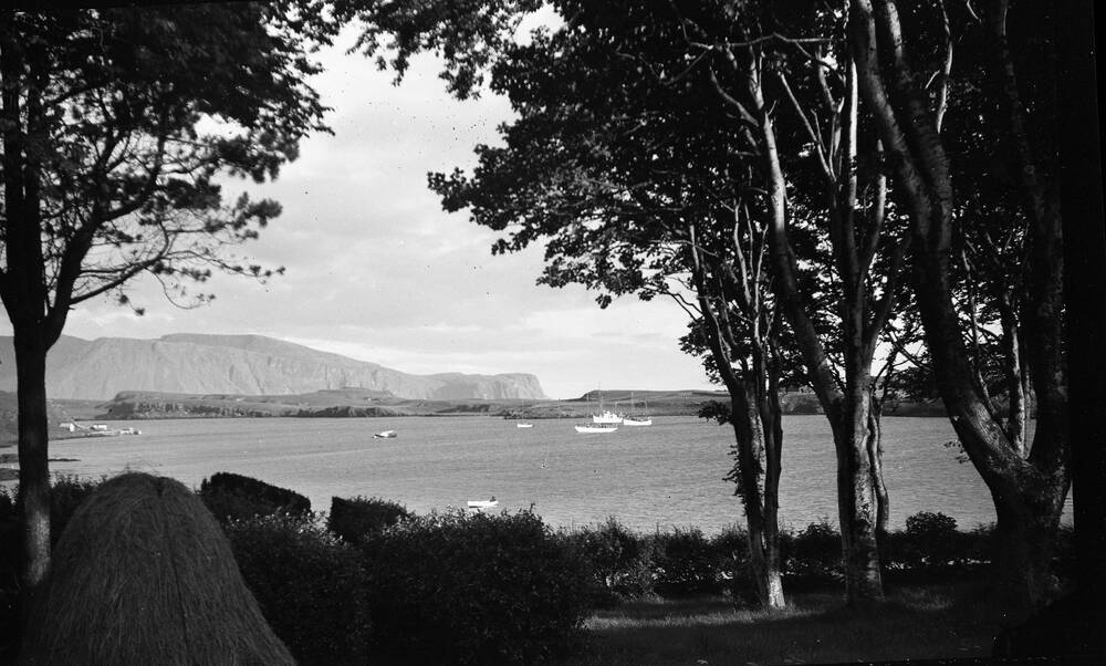 A black and white photo of Canna Bay, showing sailing boats on the water. It is framed by tall trees. Haystacks stand in the foreground, and mountains can be seen in the distance.
