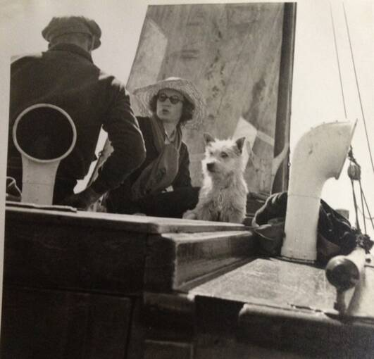 A black and white photo of two people and a dog aboard a yacht. The man sits with his back to the camera; the lady faces us but looks away.