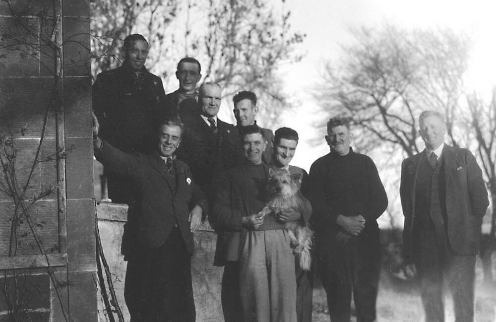 A black and white photograph of a group of 9 men, standing just outside a stone house. The man in the centre holds a small terrier dog in his arms.