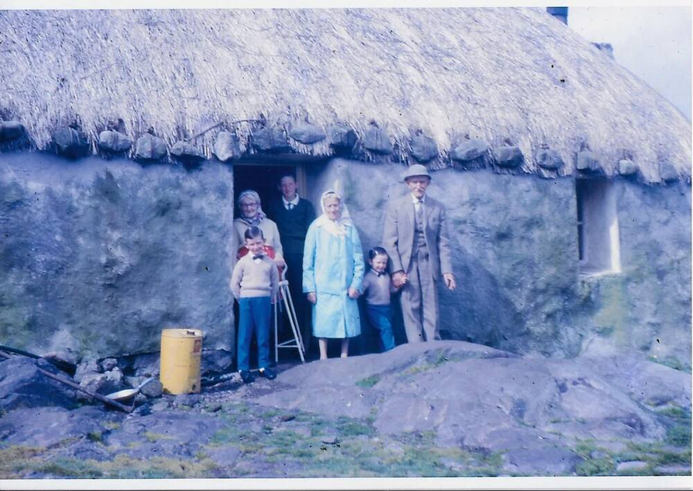 An early colour photograph of a family group standing outside a thatched stone cottage. A large yellow can is to the left of the people.