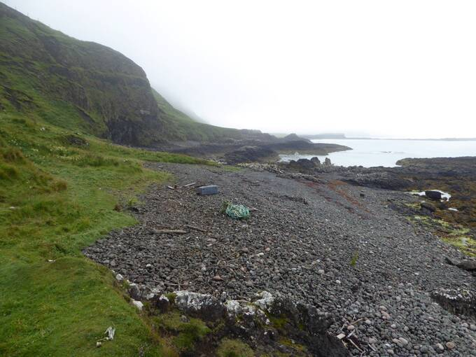 A view of a pebbly shoreline on Canna on a grey misty day. The beach is mostly clear of rubbish apart from a pile of rope at the high tide mark..