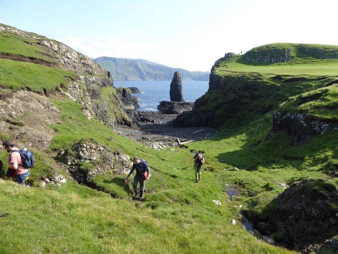 Three people make their way up a grassy cliff path from the beach on Canna, heading towards the camera. It is a sunny day. The sea can be seen in the background, with a narrow sea stack at the centre of the image.