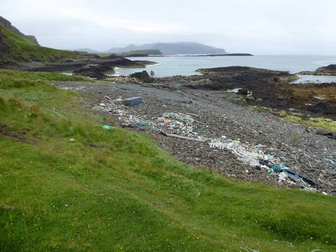 A view of a section of the Canna shoreline on a grey misty day. The pebbly beach has a large amount of rubbish, including plastic pallets, wood and rope, lying at the high tide mark.