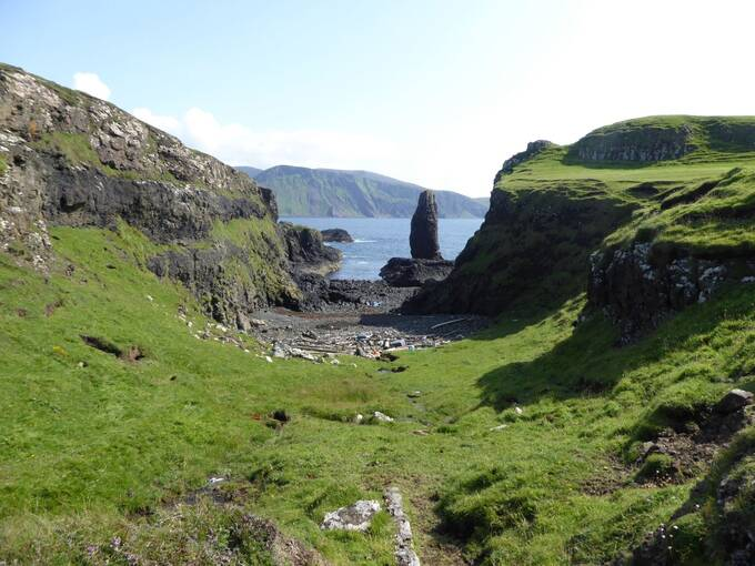 A narrow gap between grassy cliffs on Canna leads down to the sea, with a narrow sea stack providing the focal point. A lot of beach litter lies on the stony shore, caught between the two cliffs.