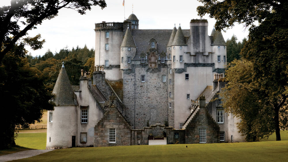An exterior view of Castle Fraser, framed by leafy tall trees.