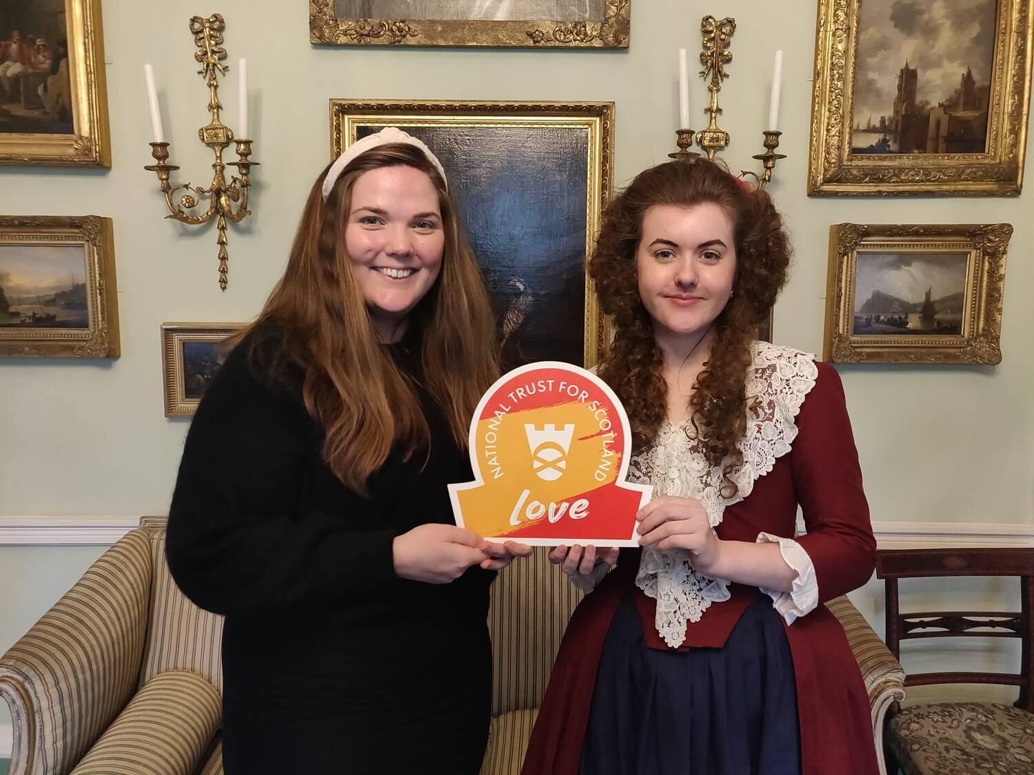 Two ladies, one dressed in Georgian clothing, hold an omega-shaped sign, saying National Trust for Scotland LOVE.
