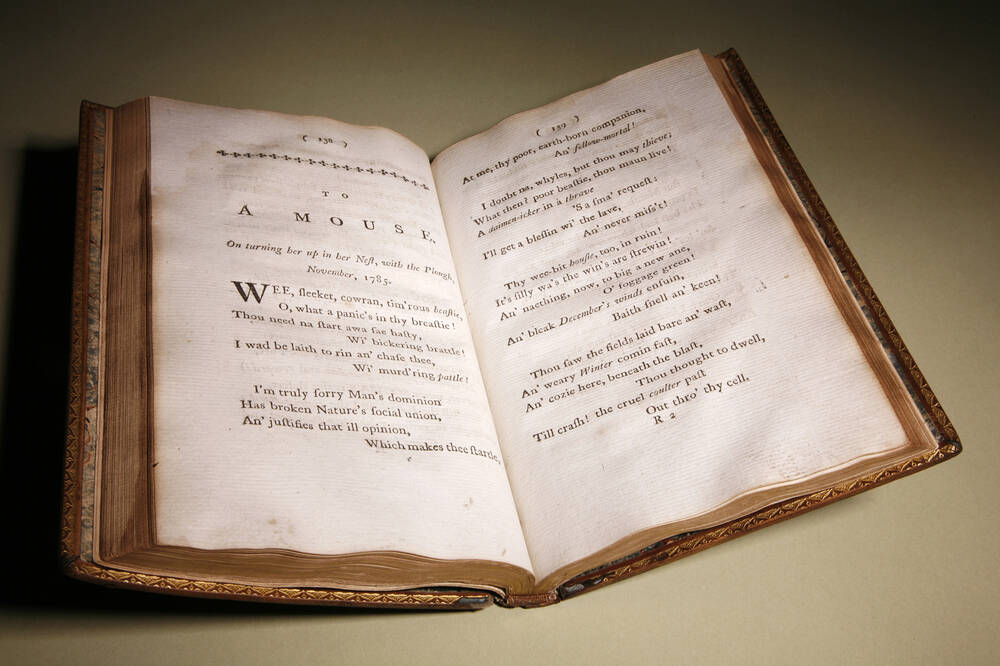 A 1786 copy of Robert Burns's 'Poems, Chiefly in the Scottish Dialect' is displayed open at the page for 'To a Mouse'.