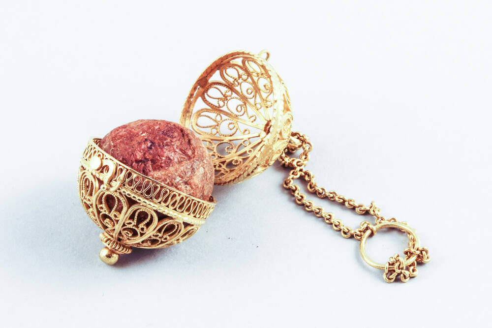 An ornate gold filigree case, containing a bold red bezoar. The case is opened wide and has a long gold chain