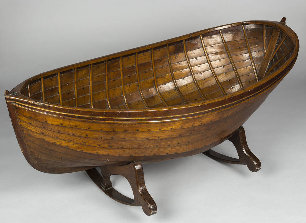A highly polished wooden cradle, shaped like a small boat, rests on a stand.