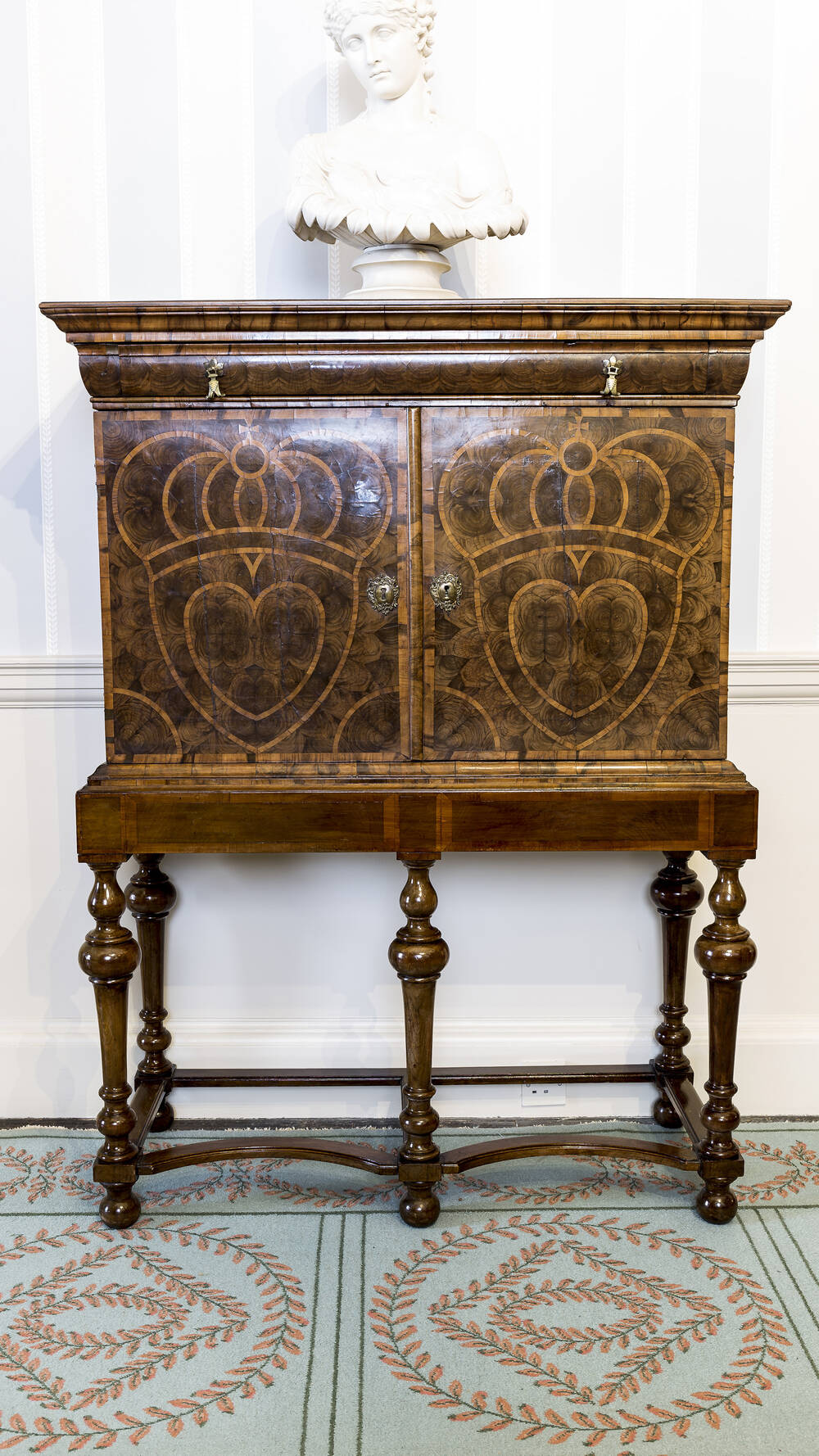 A polished wooden cabinet with six spindle legs. The doors have a heart marquetry pattern, with two metal locks. A stone bust sits on top of the cabinet.