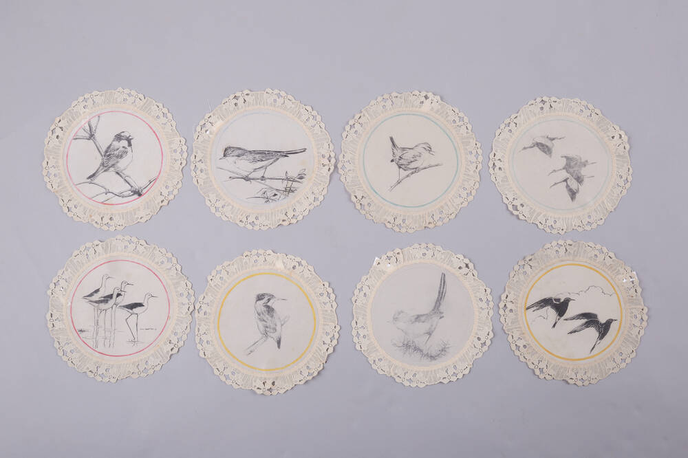 A series of 8 lace finger mats are displayed. Each contains a hand-painted black and white bird illustration.