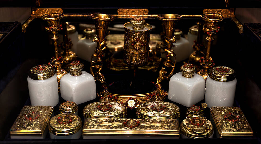A very elaborate and ornate dressing case, filled with ceramic pots and gilt slim cases. Many of the lids are encrusted with red jewels.