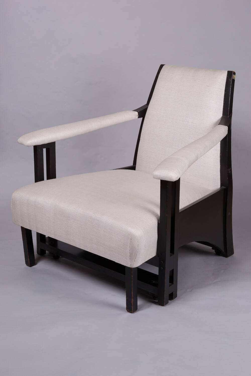 An easy armchair, designed by Charles Rennie Mackintosh. It has a dark wooden frame, with white linen-style padded sections.