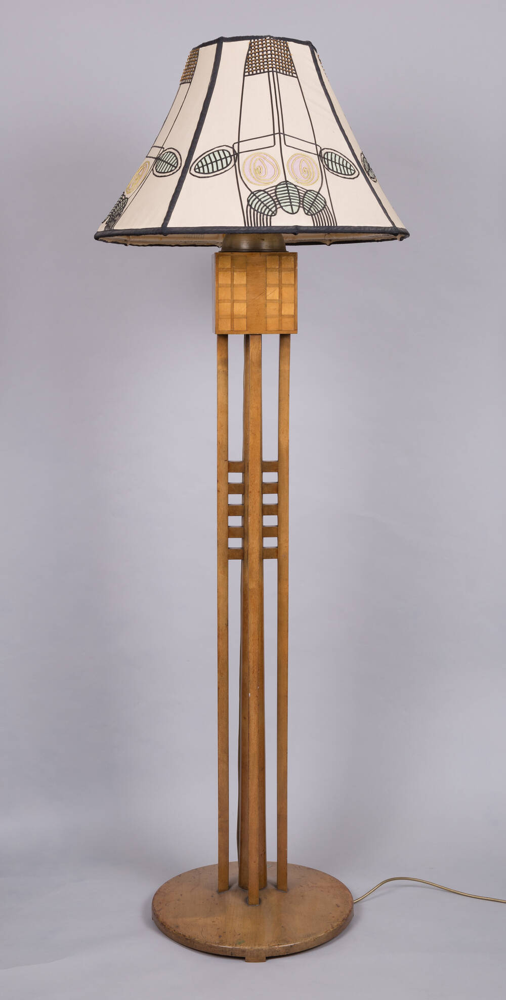 A standard lamp designed by Charles Rennie Mackintosh. It has a wooden stem, and the shade features the Mackintosh rose design.