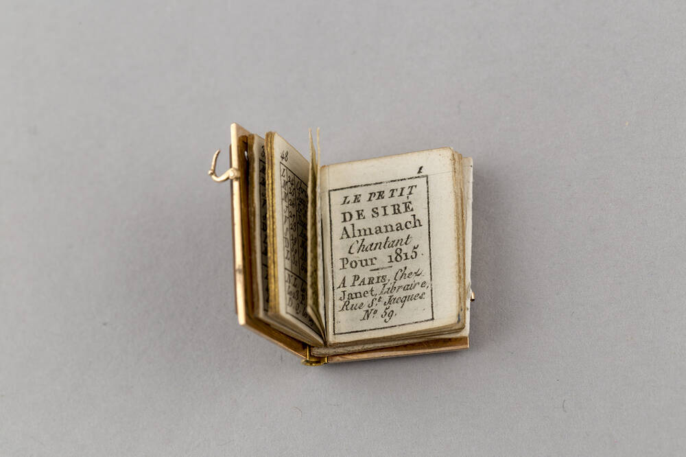 A very small book is displayed open at a page with French text upon it: Le Petit Desire Almanach Chantant pour 1815 | A Paris, chez Janet, Libraire, Rue St Jacques, No. 59. The side of the book has a tiny metal clasp.