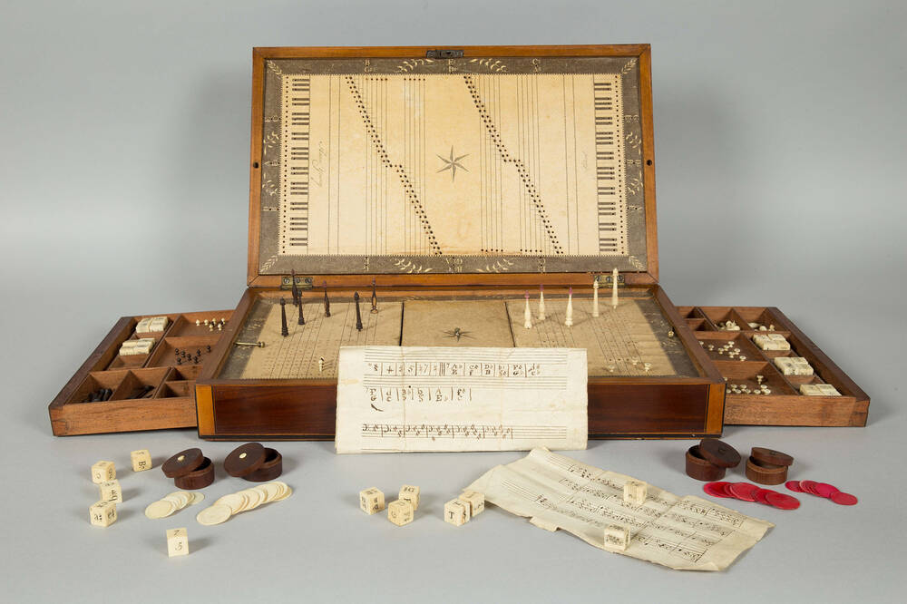 A polished wooden box is opened up, showing a musical board game. It has drawers either side, which are also open to show various pieces. Dice, counters and instructions are laid out in front of the box.