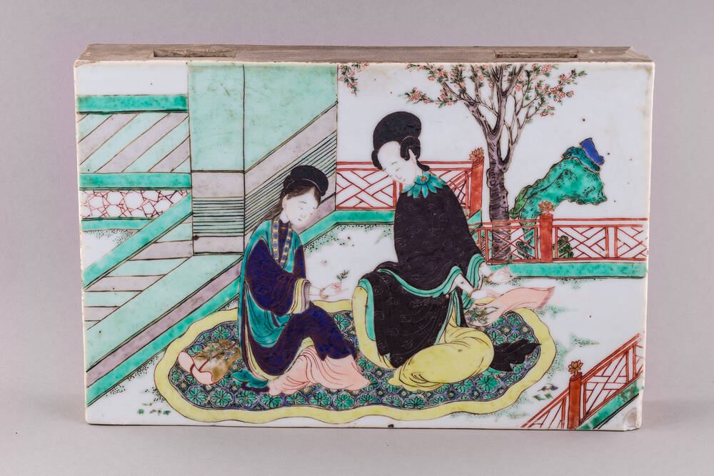 An 18th-century Chinese porcelain tile, decorated with a painting of two people sitting on a carpet in a garden.
