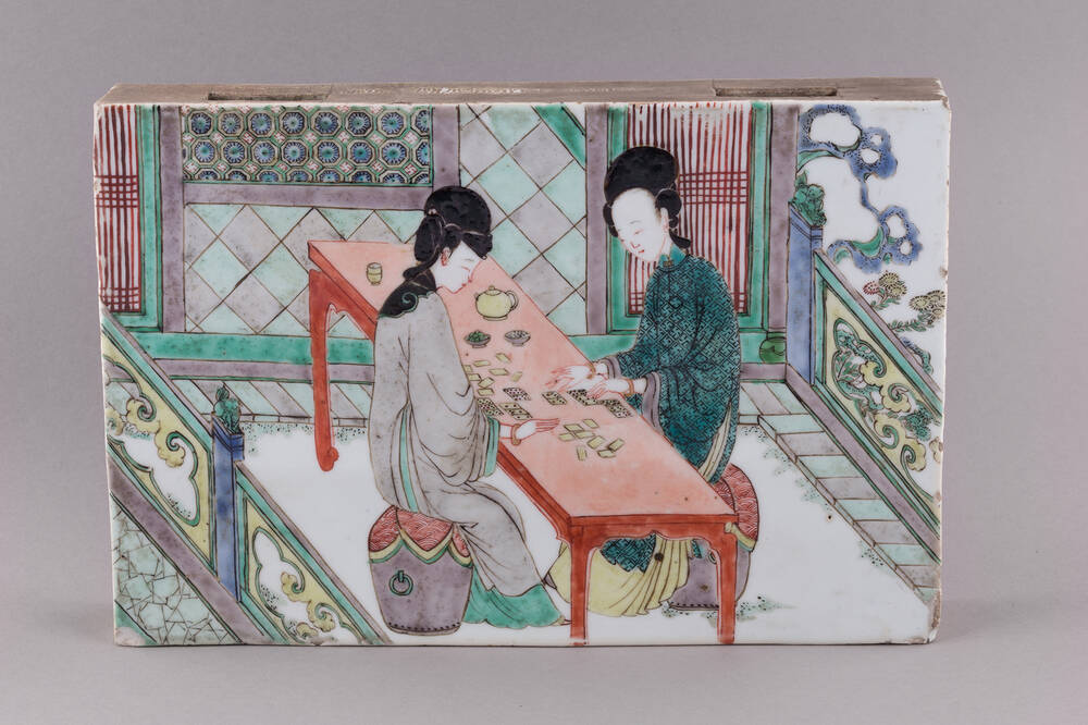 An 18th-century Chinese porcelain tile, decorated with a painting of two people playing dominoes on either side of a long red table.