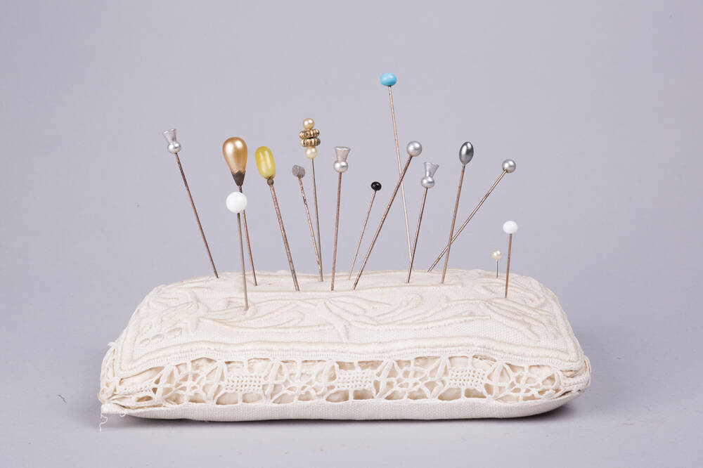 A white silk pin cushion with a lace-effect pattern around the outside. Sticking up out of it are 15 beautifully delicate and ornate hat pins.