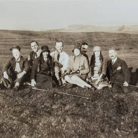 A black and white photo of a group of men and women sitting on a golf course